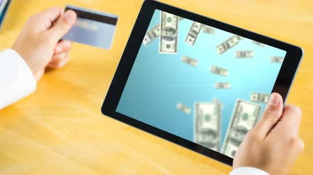 job transfer : businessman holding digital tablet showing animated dollar bills and credit card