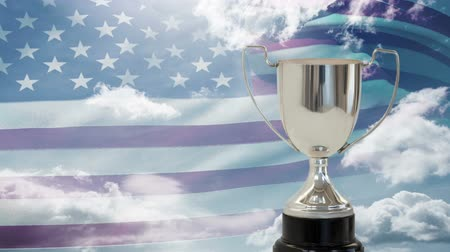 ösztönző : Animated Trophy against animated american flag blowing in the wind and a blue sky background Stock mozgókép