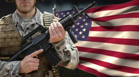 bulletproof : Soldier with weapon against american flag blowing in the wind background Stock Footage