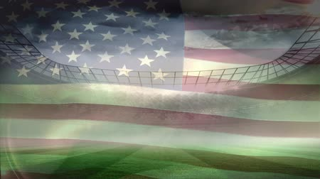 american football player : American flag blowing in the wind against football stadium background