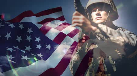 ordu : American flag blowing in the wind against soldier background Stok Video