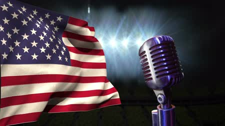 честь : American flag blowing in the wind against nightsky background with microphone in the forefront Стоковые видеозаписи