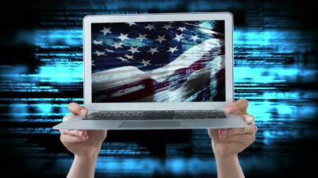 кодирование : Hand holding Laptop showing American flag against blue animated background