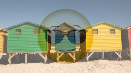 emoticono : Emoticon amarillo animado con gafas de sol contra el fondo de casas de playa Archivo de Video