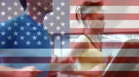 освещенный : Man and woman working out at the gym with headphones against animated american flag background
