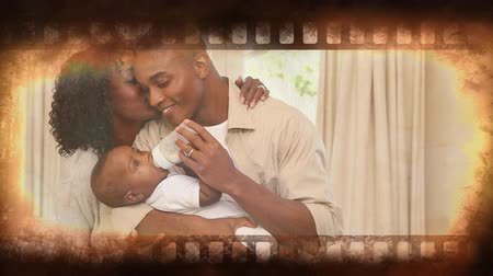 film camera : Film strip showing happy family caring for baby Stock Footage
