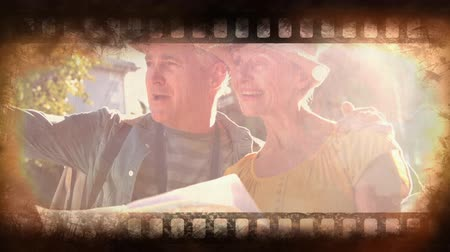 yüksek çözünürlüklü : Old Movie tape showing happy older couple with map exploring Stok Video