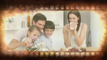 освещенный : Old Movie tape showing happy family in the kitchen having breakfast