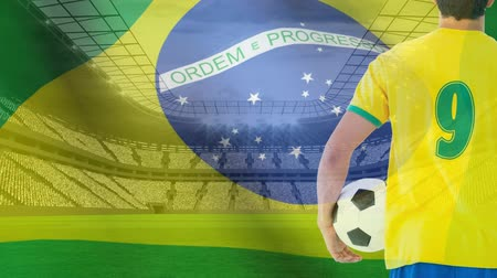 futbolistas : Brazil Flag blowing in the wind at stadium with football player holding football