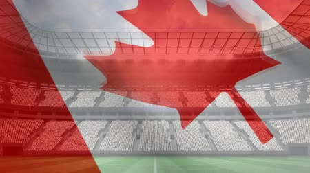 честь : Digital composite of Canadian flag waving in the wind in front of full football stadium