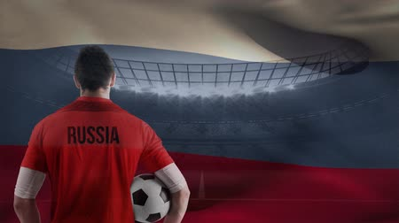 trikot : Russian soccer player holding ball with Russia flag waving in the wind against soccer stadium lights at sunset