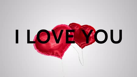 casamento : Slogan I love you in big letter on a clean background with two heart balloon that appear and fly
