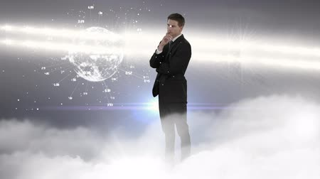seçme : Businessman watching and touching the digital earth in front of him on a grey background with mist