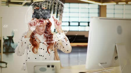 interativo : Woman with virtual reality headset looking and touching at a digital earth with data on her office