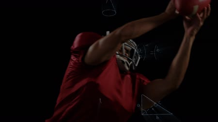 abilities : Digital composite of front view of american football player jumping and catching a ball against a black background with maths equations. In slow-motion Stock Footage