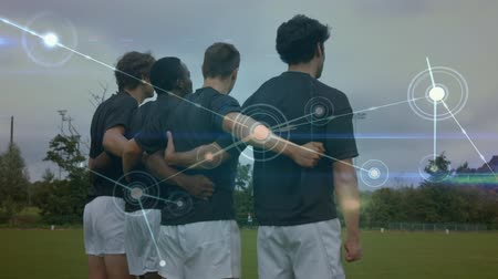bekötött : Digital composite of rugby players holding each others against network connection lines background Stock mozgókép