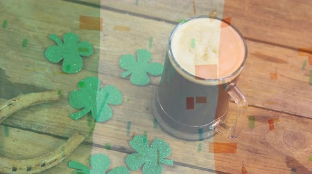 lucky charm : Digital Composite of mug of beer, shamrock & horseshoe for St Patricks Day on wooden table against illustration of confetti Stock Footage