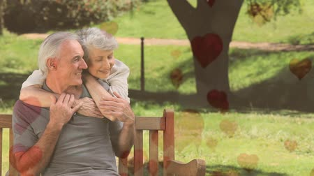 bekötött : Front view of happy senior couple sitting on a bench in  park with hearts moving upwards in foreground