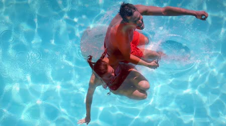 companionship : Digital composite of caucasian couple jumping on swimming pool with red heart on foreground Stock Footage
