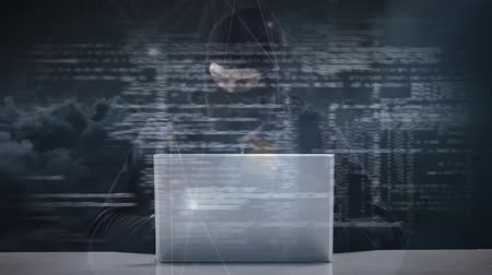 intruder : Digital composite of hacker in ski mask typing on laptop while looking around nervously against illustration of digital code data and clouds background Stock Footage