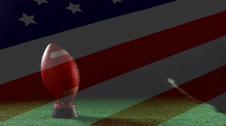 rúgbi : Digital composite of American football player kicking in the ball with the American flag in transparency Vídeos