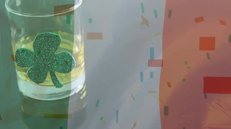 st patrick : Digital composite of a whisky glass with a shamrock on an animated Irish flag background with colorful confetti falling on the foreground for St Patricks Day Stock Footage