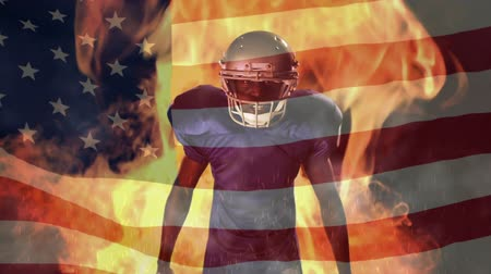 fury : Digital composite of an angry African American quarterback standing with the ball and looking at the camera with an American flag on the foreground and a fire burning on the background Stock Footage