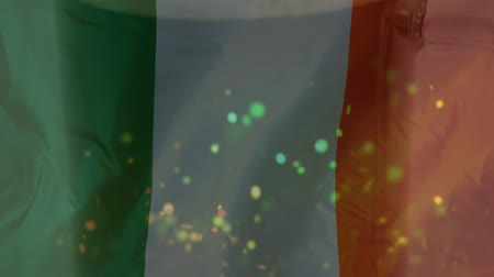 quartilho : Digital composite of a beer pint standing against an Irish flag waving on the background with colourful confetti flying on the foreground for St Patricks Day Stock Footage