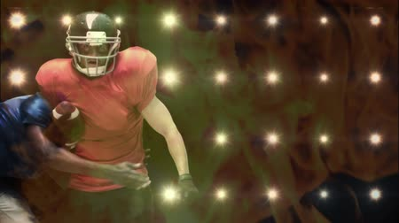 снасти : Digital composite of Caucasian male football player tackled by an African American male football player against background with lights and fire animation on the foreground