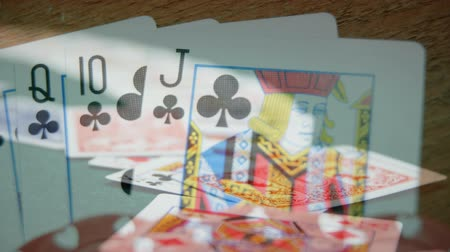 croupier : Digital composite of suite of high clover cards next to chips on wooden table with  cards on the foreground