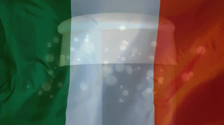 trojlístek : Digital composite of translucent Irish flag with glass of beer and light effects on the background for St Patricks Day Dostupné videozáznamy