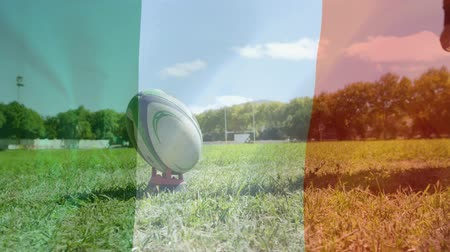 тройник : Digital composite of Irish Caucasian rugby player kicking the ball and Irish flag waving on the foreground