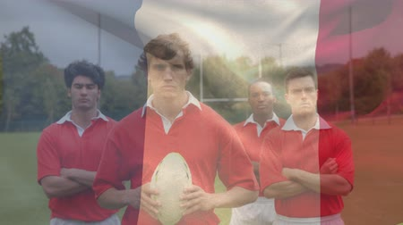 french team : Digital composite of a multi-ethnic rugby team standing on field and looking at the camera with a French flag waving on the foreground Stock Footage