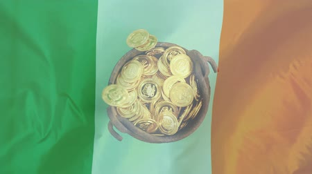 trojlístek : Digital composite of gold coins falling in cauldron with an Irish flag waving on the background for St Patricks Day Dostupné videozáznamy