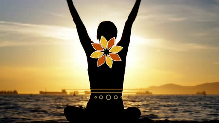 cross legged : Digital composite of woman doing the lotus pose in yoga while calmly meditating at sunset. Lotus animation coming up in the middle of the screen