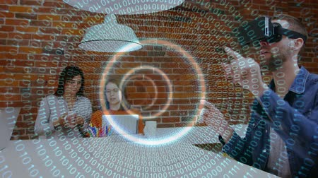 wizualizacja : Digital composite of handsome Caucasian male using virtual headset and female executives working on laptop. Light tunnel is on the foreground Wideo