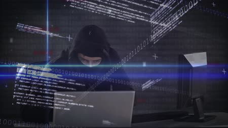 korsanlık : Digital composite of smart Caucasian hacker with balaclava and black sweater hacking  computer while coding moves on the foreground.