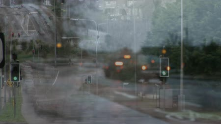 sokak lâmbası direği : Digital composite of cars waiting in front of traffic lights and cars driving into traffic jam against city background Stok Video