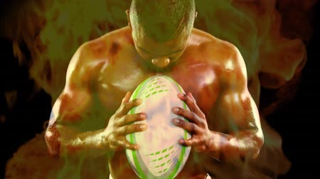 rúgbi : Digital composite of handsome African American rugby player holding football while screaming loudly and fire burning on the foreground against black background