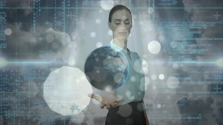 concentrando : Digital composite of pretty Caucasian businesswoman holding digital globe while digital binary interface moves on the background in office. Light effects moves on the foreground. Vídeos
