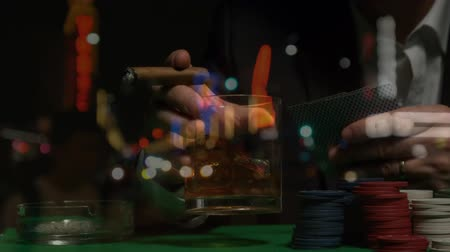 bogaty : Digital composite of mature man holding cigar and alcoholic beverage in one hand while holding game cards in the other hand at poker table in Las Vegas. Poker chips lying on the table.