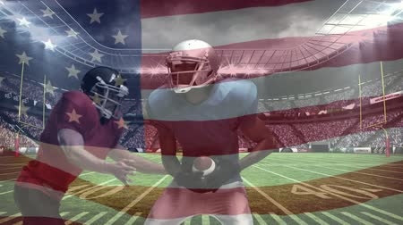 american football player : Digital composite of African American rugby player catching football while another African American rugby player tackled him down and American flag waving in background in full stadium