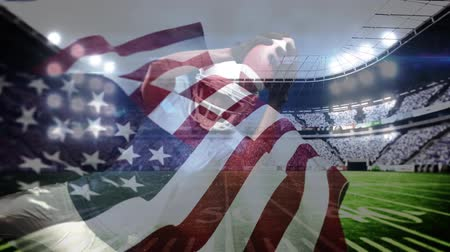 jump away : Digital composite of African American rugby player catching football and American flag waving on the foreground in stadium. Rugby player dives to catch the ball and stadium lights in the background. Stock Footage