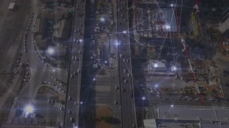 kavrama : Digital composite of aerial view of cars driving on the high way while dots connected by lines moves on the foreground Stok Video