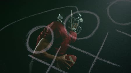 american football player : Digital composite of active African American rugby player running with football while strategy paper moves on the foreground. Stock Footage
