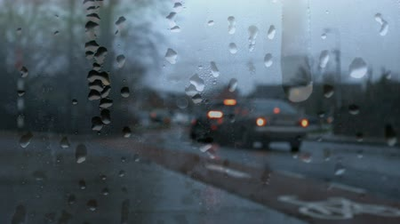 kavrama : Digital composite of camera recording cars driving on city road while it is raining. Lens of camera has water drops on it.