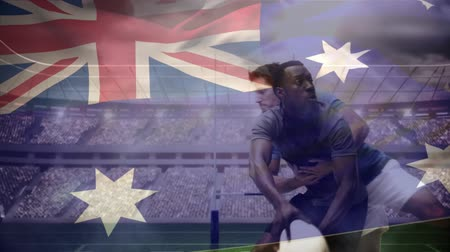 společenství : Digital composite of African American rugby player throwing the football away while being tackled down by Caucasian rugby player and Australian flag waving on the foreground in stadium Dostupné videozáznamy