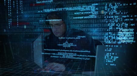 roubo : Digital composite of smart Caucasian hacker using computer to hack into the system while digital codes move on the foreground Stock Footage