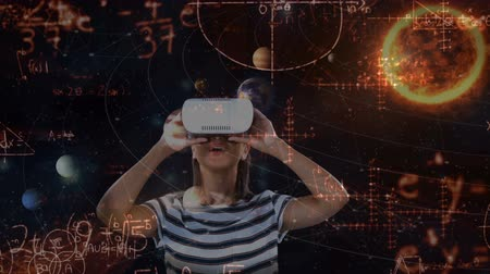venuše : Digital composite of Caucasian girl wearing virtual reality headset while mathematical formulas move on the foreground against universe with planets background 4k