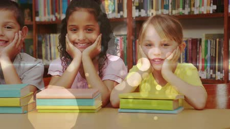 educar : Front view of three multi ethnic schoolgirls leaning on a table and looking at the camera with books in front of them in a library against bookshelf in background